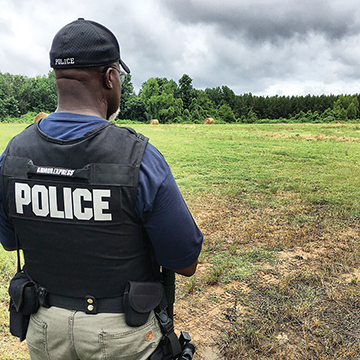 Phillip Brackett watches an open field on the edge of the woods as teams of officers search the area for Adrian Golden, the man wanted for the shooting of Kimberly Sisk last Thursday.