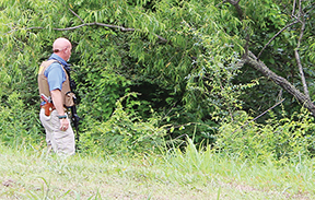 Sheriff Greg Pollan patrols the edge of a large ditch as searchers with dogs walk through the interior of the woods.